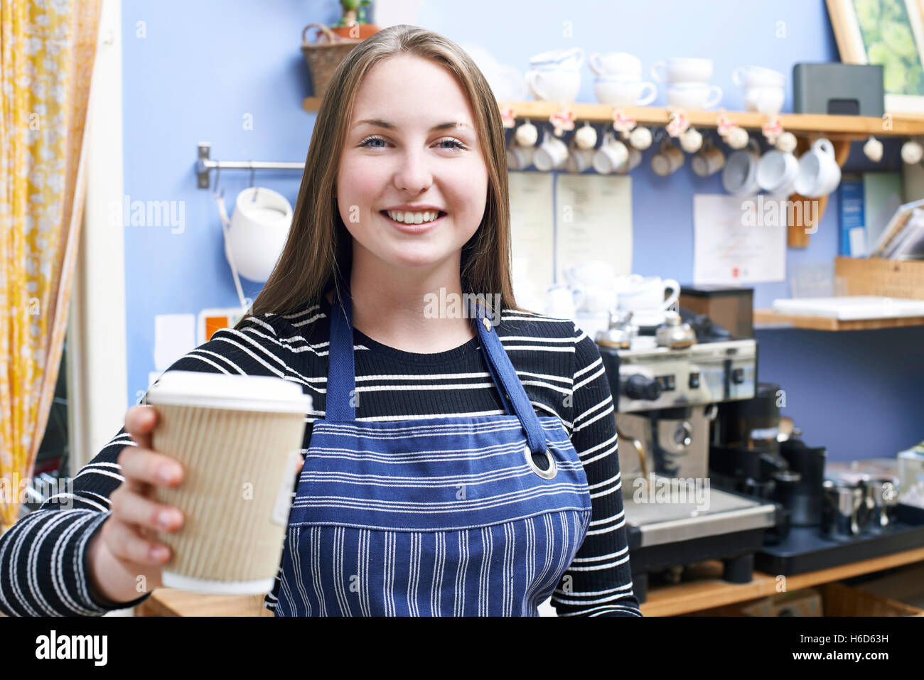 Waitress In Cafe Serving Customer With Takeaway Coffee - Stock Image