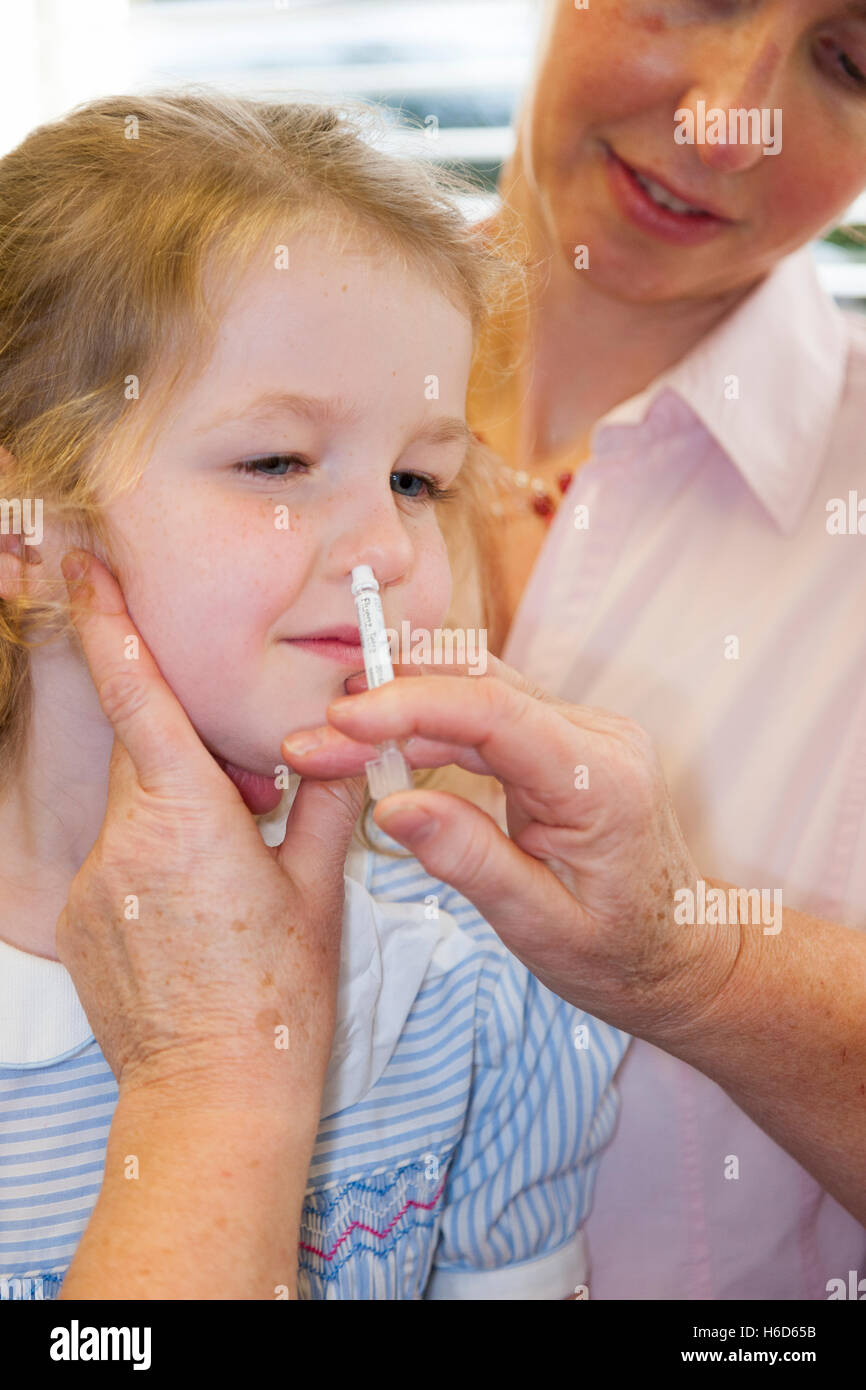 4 year old child, with her mum / mother, receives dose of Fluenz flu vaccine nasal spray immunisation from NHS Practice Stock Photo