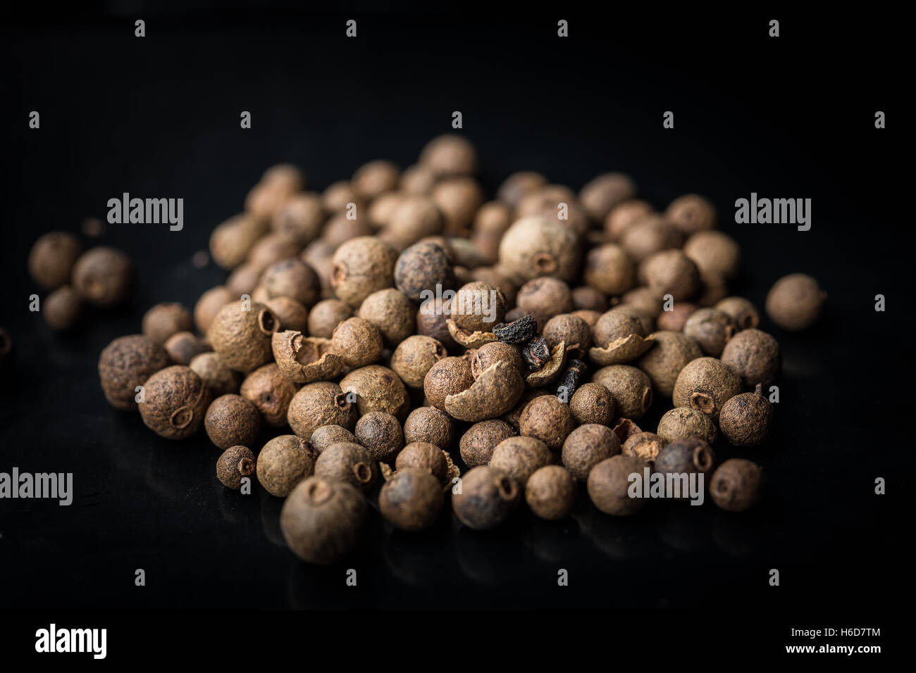 Pimento berries on black background - Stock Image