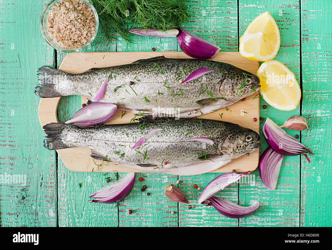 Gutted trout on a bright wooden background. Top view - Stock Image