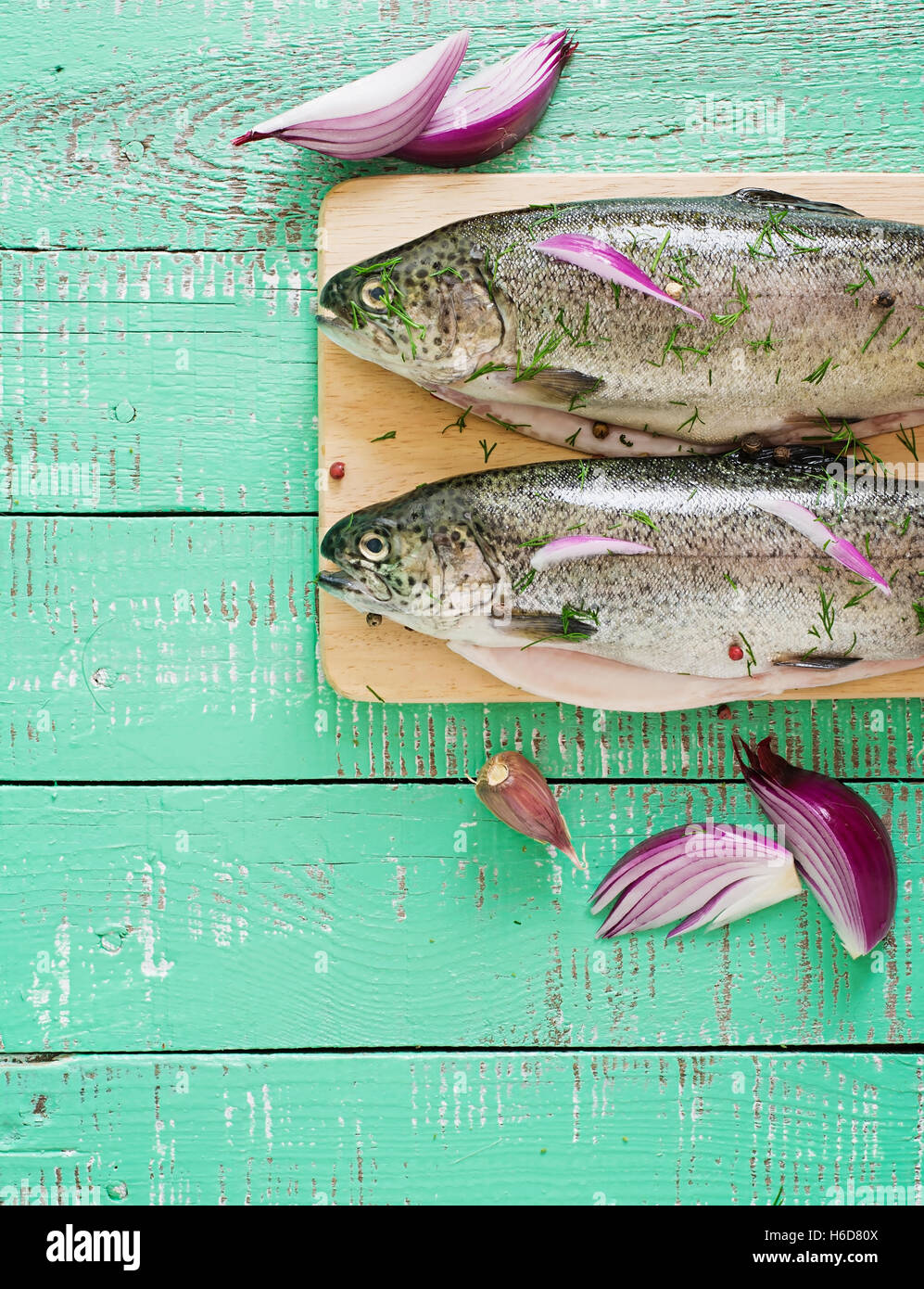 Gutted trout on a bright wooden background. - Stock Image