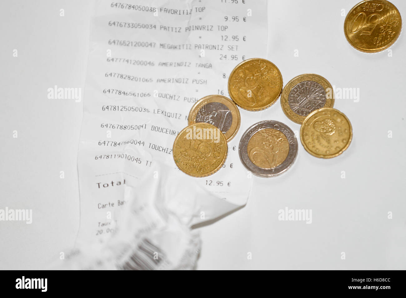 Store bill and euro coins on white background - Stock Image