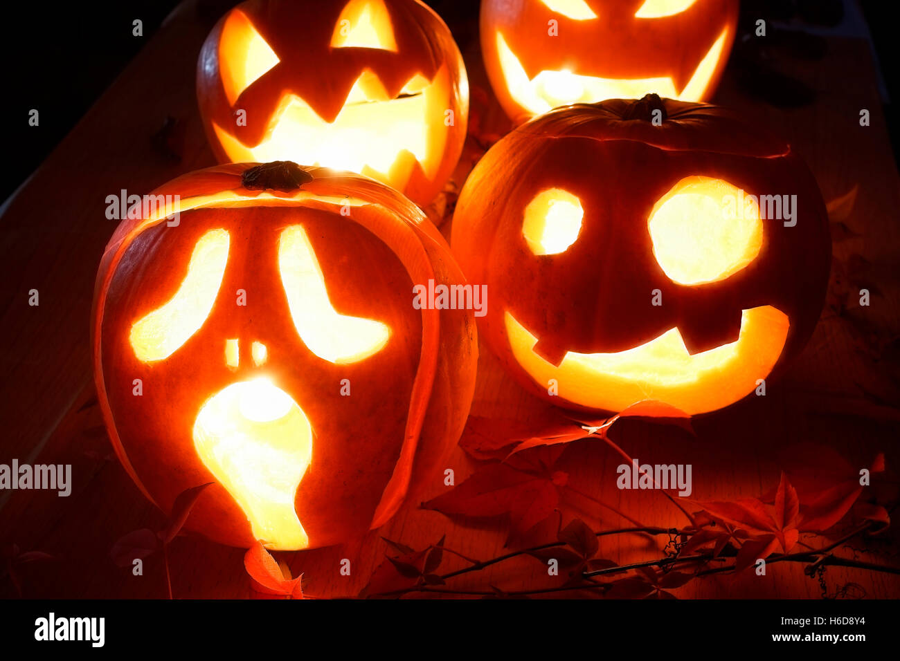 Scary Halloween Pumpkins With Eyes Glowing Inside At Black