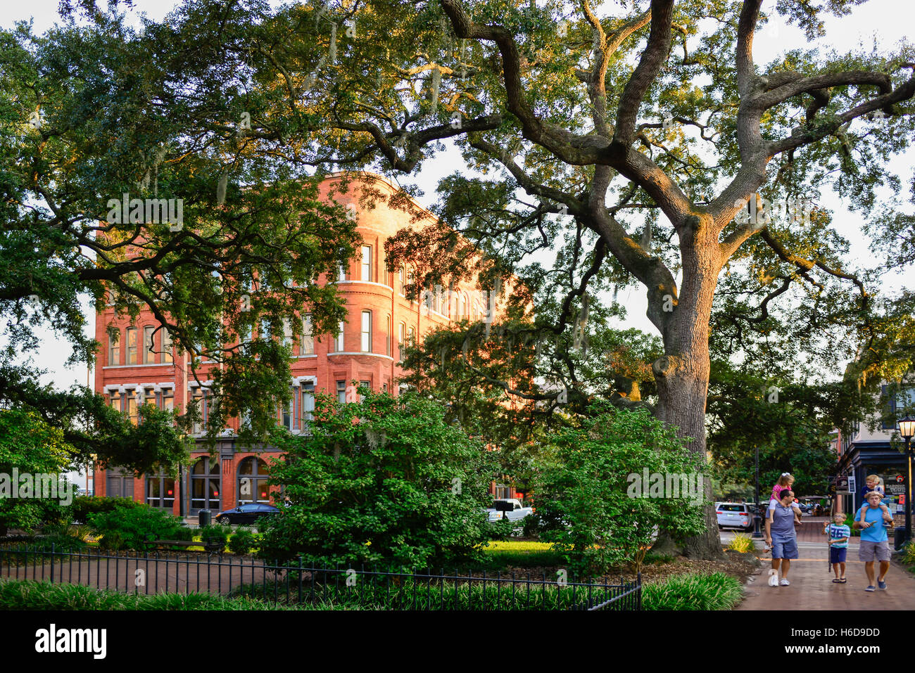 Family enjoys the stroll near Savannah College of Art and Design's Romanesque Revival Style Posetter Hall shrouded Stock Photo