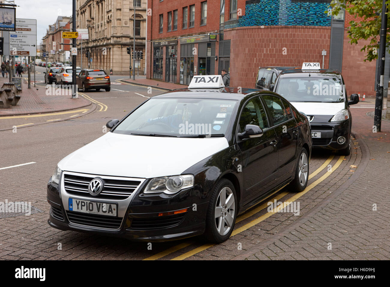 black and white taxis on a cab rank in cardiff wales. Black Bedroom Furniture Sets. Home Design Ideas