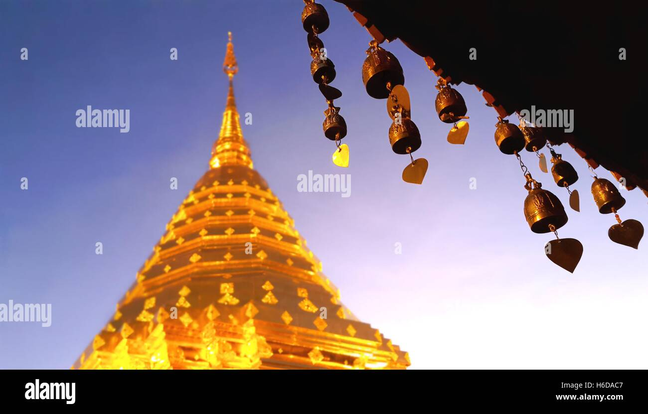 Buddhist brass bell  at the roof of thai temple with soft blurred golden stupa, Wat Phra That Doi Suthep, Chiang - Stock Image