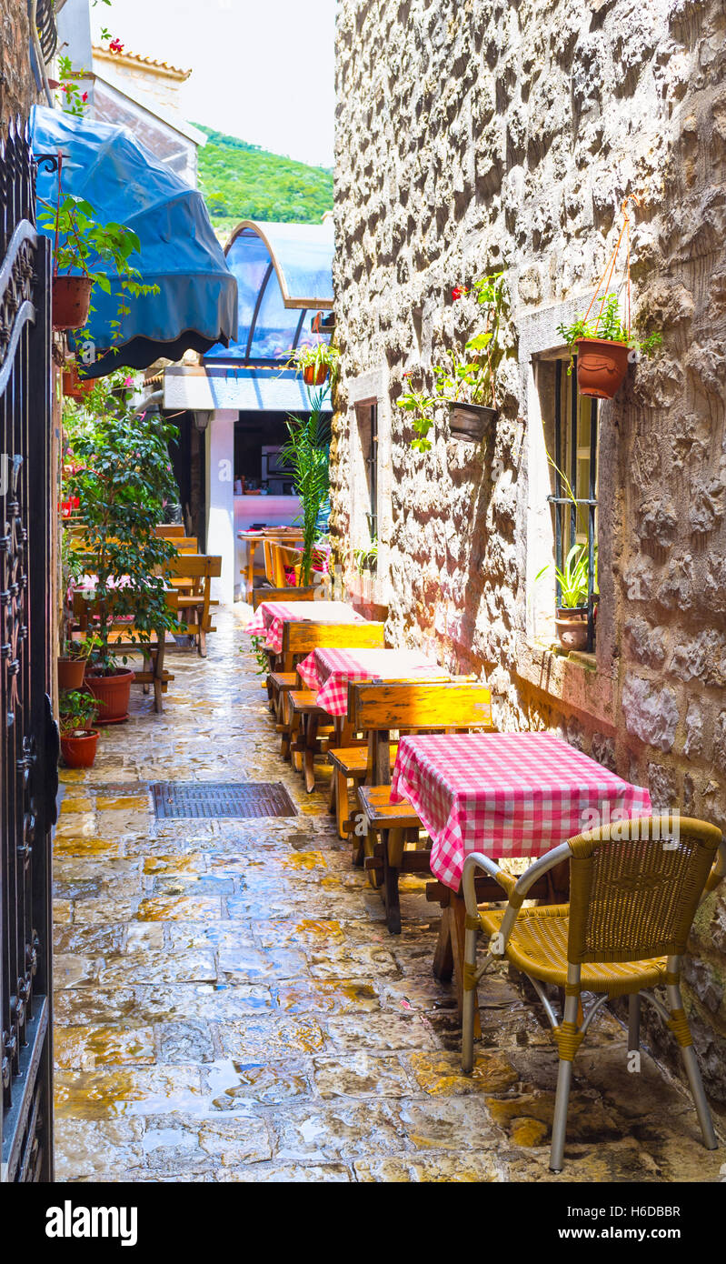 The street cafe located in the narrow lane in the old town of Budva, Montenegro. Stock Photo