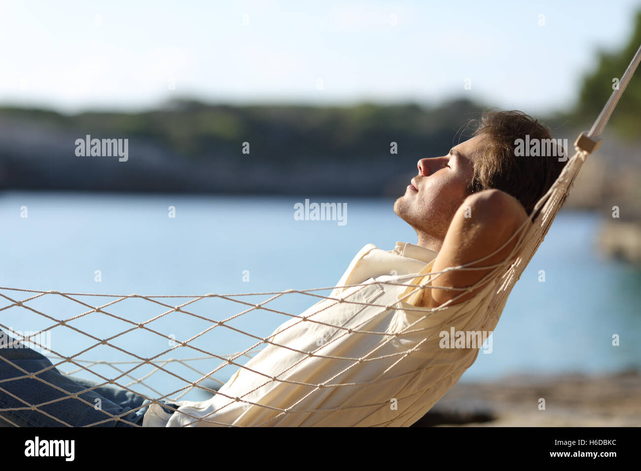 Side view of a casual happy man relaxing on a hammock in the beach on holidays - Stock Image