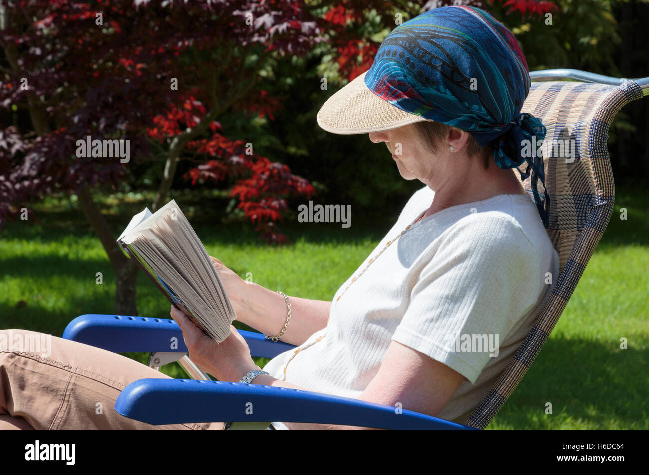 Someone retired senior woman relaxing in a backyard garden chair reading a book in summer sunshine shaded by sunhat. - Stock Image