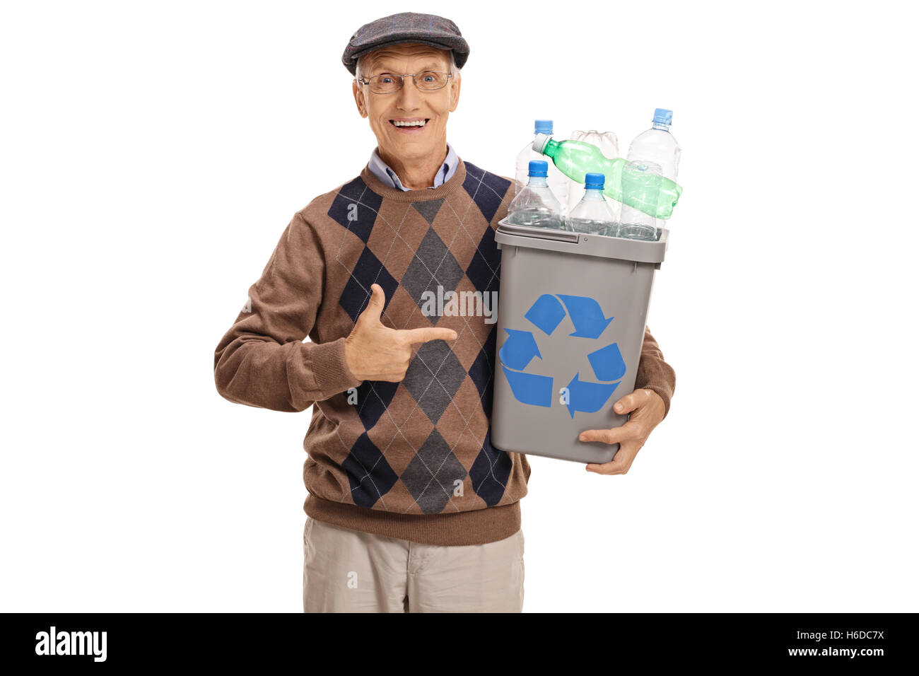 Cheerful elderly man holding a recycling bin full of plastic bottles and pointing isolated on white background - Stock Image