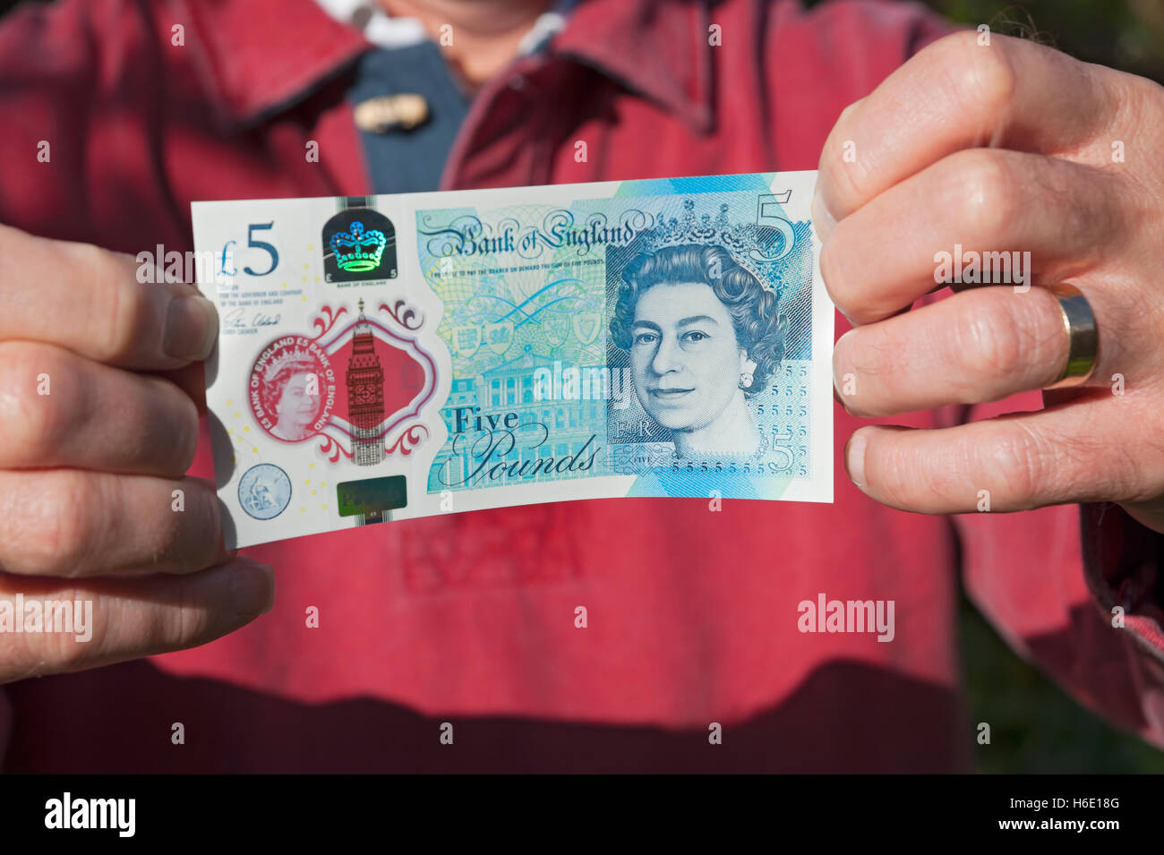 Man holding new polymer five pound note England UK United Kingdom GB Great Britain - Stock Image