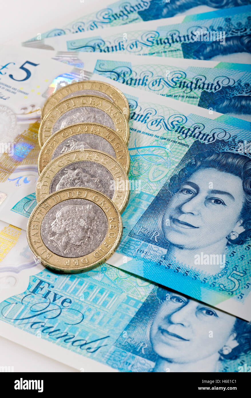 New polymer five pound notes and two pound coins England UK United Kingdom GB Great Britain - Stock Image