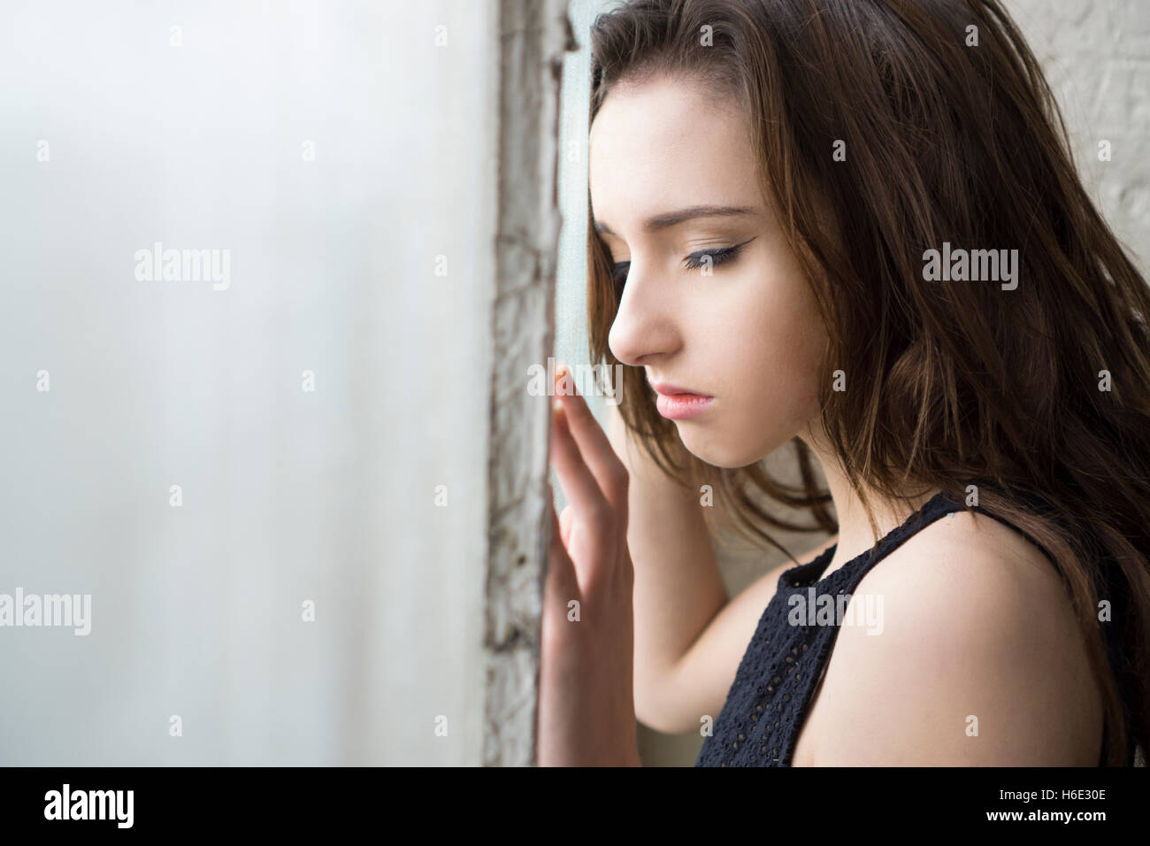 Sad young woman standing by the window Stock Photo