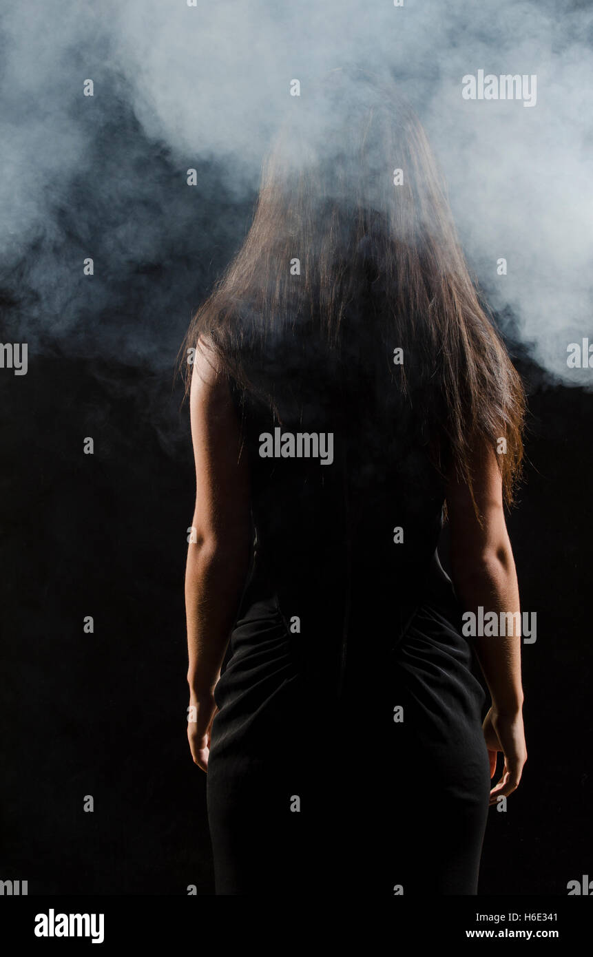Mysterious female figure standing in the fog - Stock Image