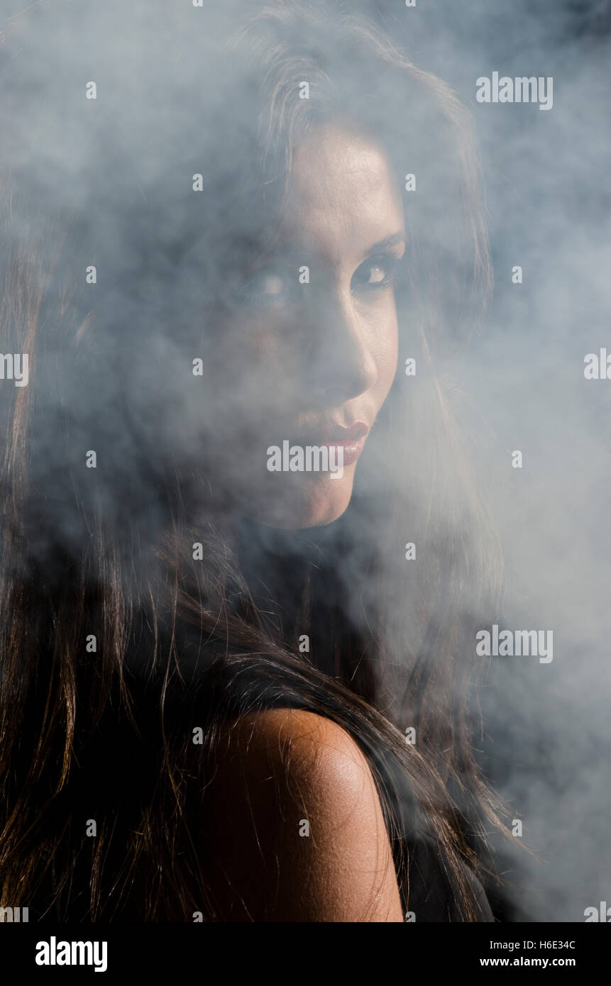 Beautiful young woman standing in the dark with smoke - Stock Image