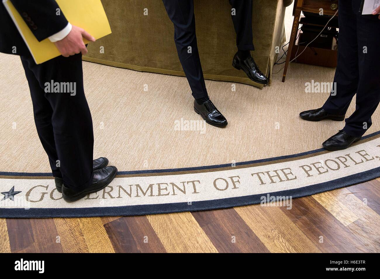 A view of the feet of U.S. President Barack Obama as he talks to senior advisors in the White House Oval Office - Stock Image