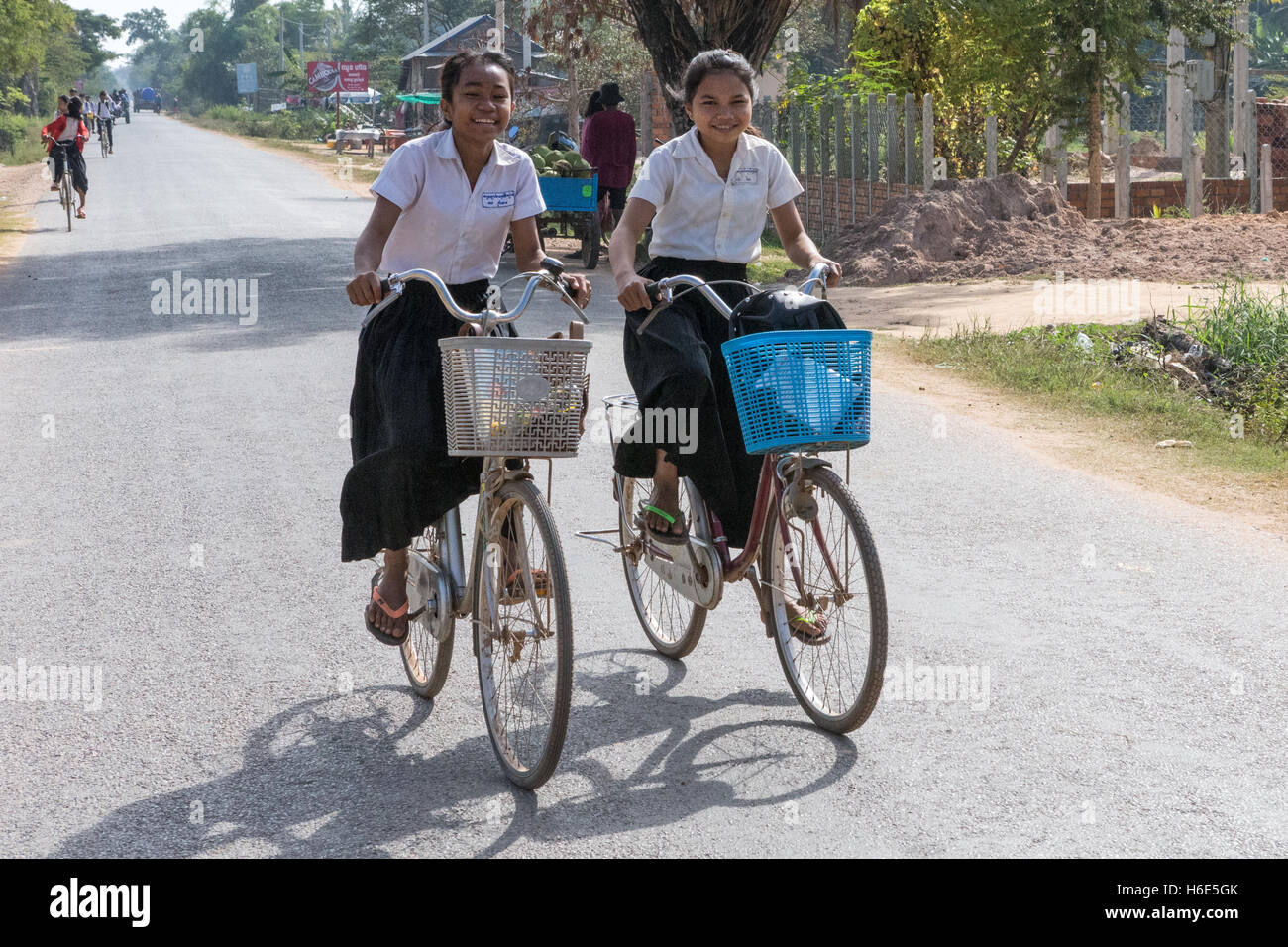 2 girls bicycling home from school Cambodia - Stock Image
