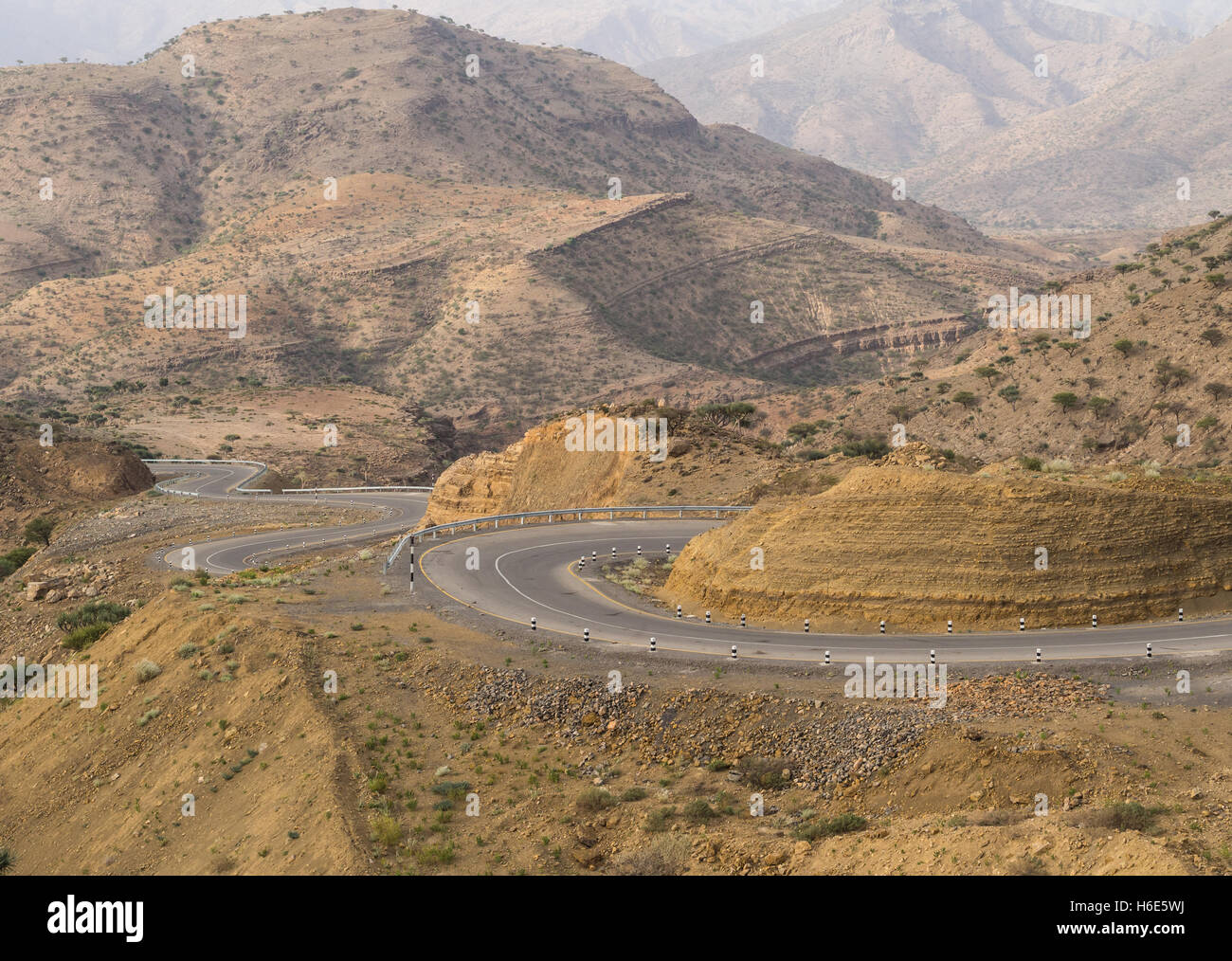 Road running through dry landscape in Ethiopia in July. - Stock Image