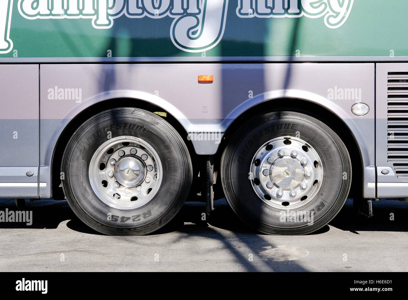 Twin axial view of a passenger coach seen in a parked position with livery of the tour operator. - Stock Image