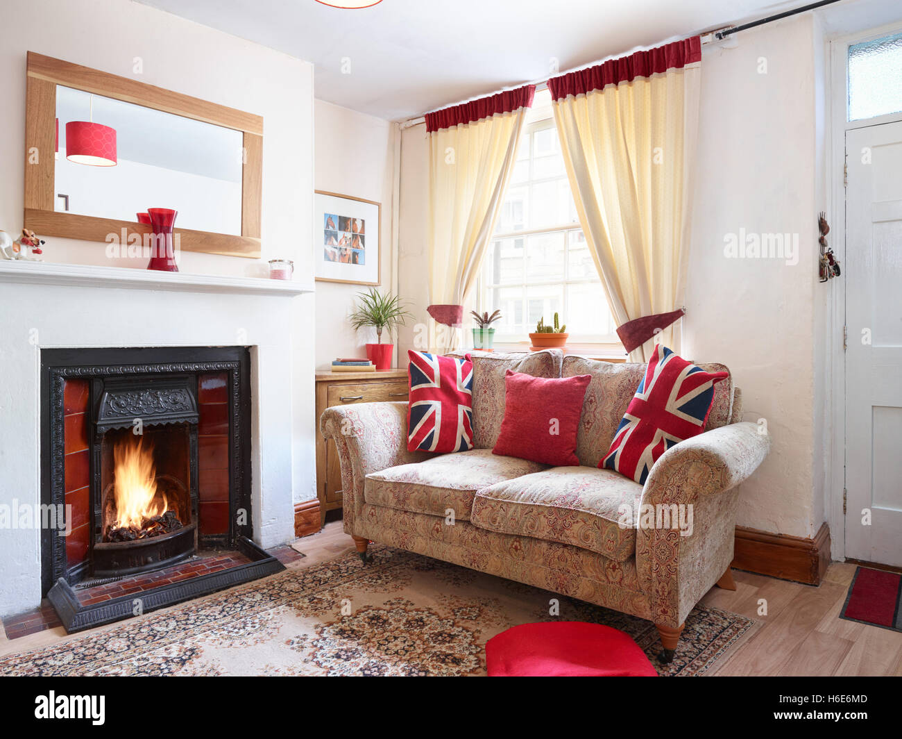 A cosy, small UK living room with roaring fire & sofa adorned with patriotic cushions - Stock Image