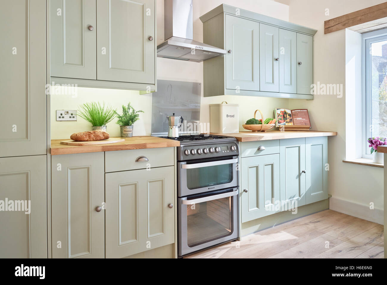 A contemporary, fresh open plan kitchen incorporating an integrated oven, cooker, hood & wood work surfaces. - Stock Image
