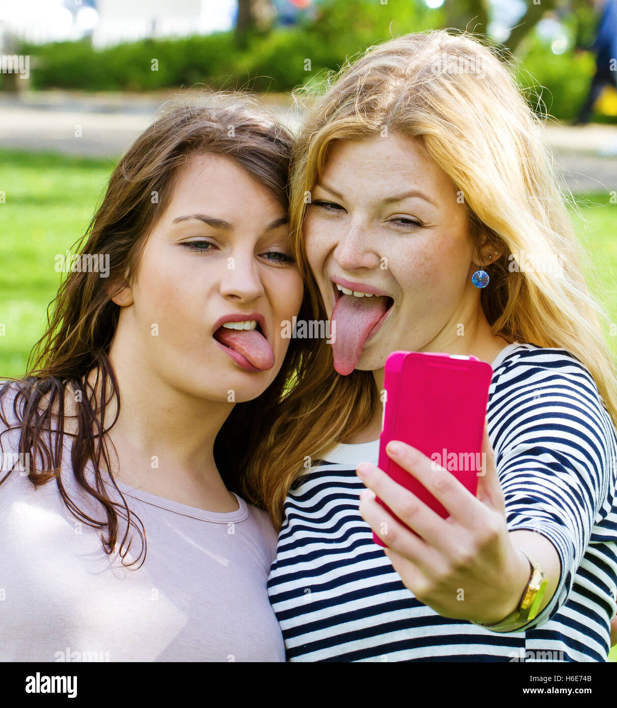 Girls taking a funny selfie and sticking tongue out - Stock Image