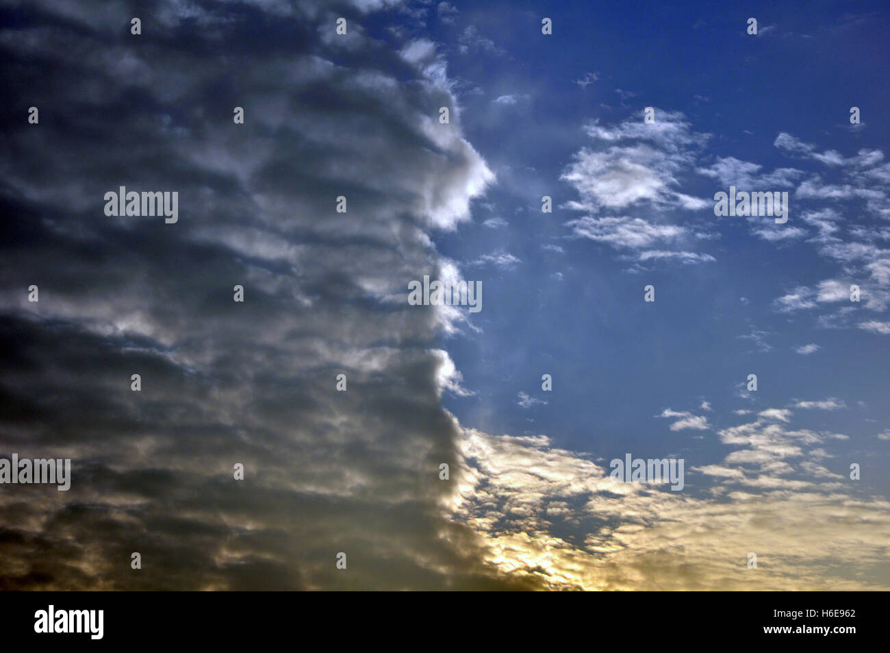 Clouds divided sky during sunset colorful light against dark - Stock Image