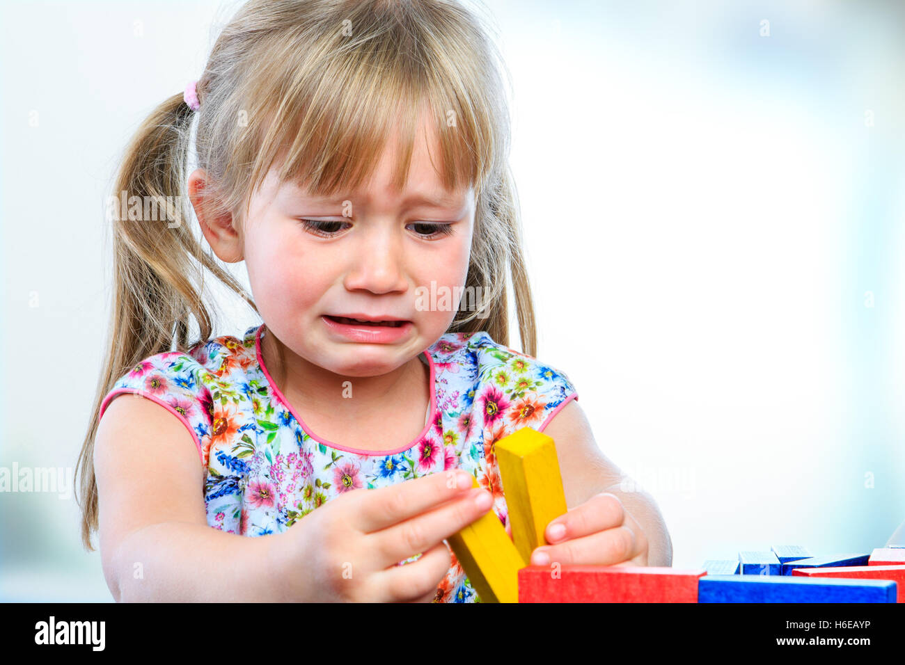 Close up portrait of crying little girl playing with wooden blocks at table.Frustrated girl showing moody behavior - Stock Image