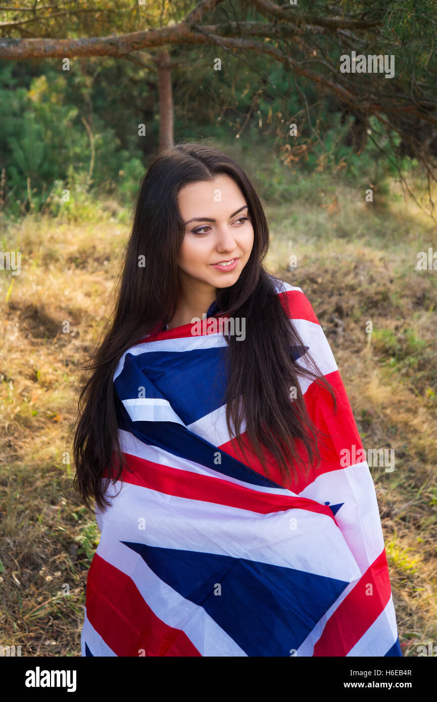 Young beautiful brunette girl posing with a British flag in autumn park - Stock Image