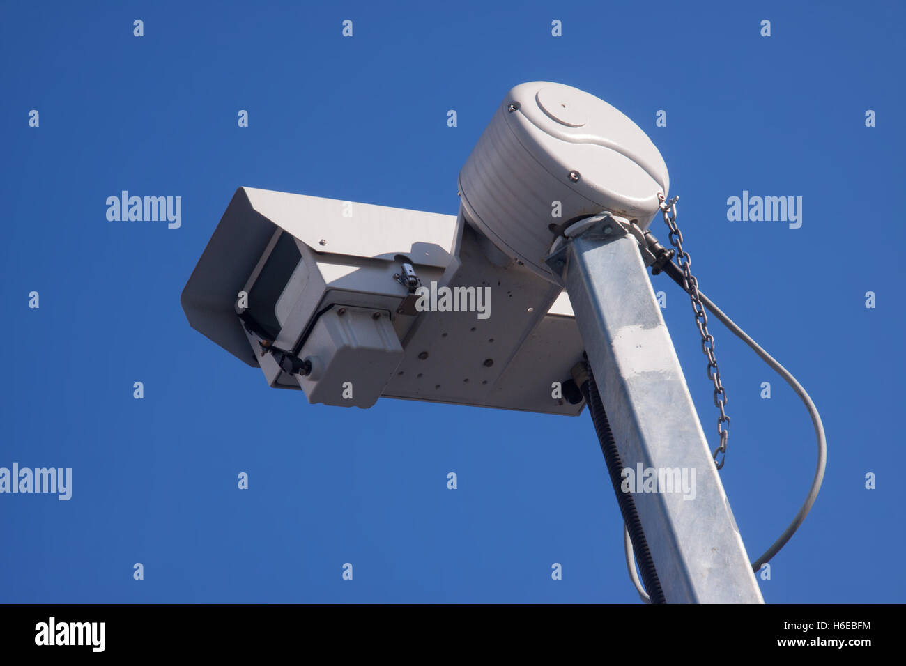 A closed circuit television camera cctv against a clear blue sky - Stock Image