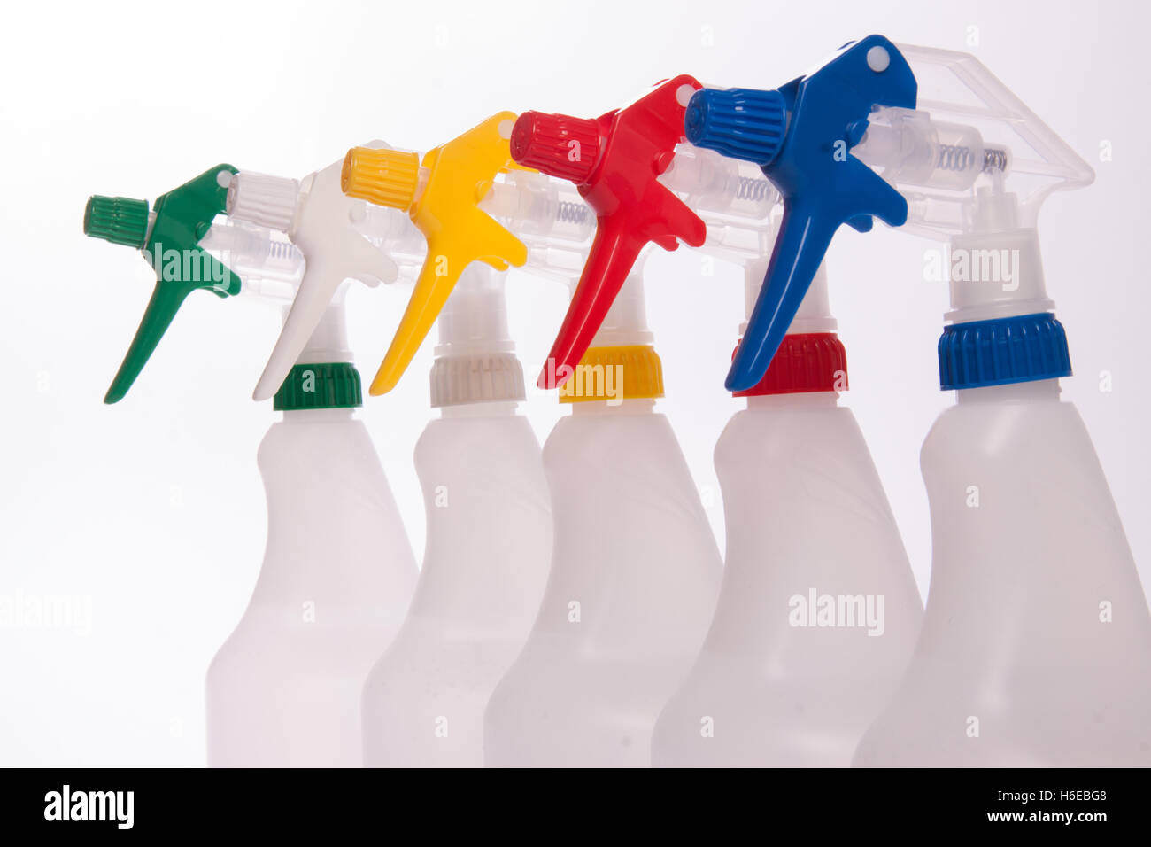 Trigger spray bottles, hand held sprayers in green white yellow red and blue - Stock Image