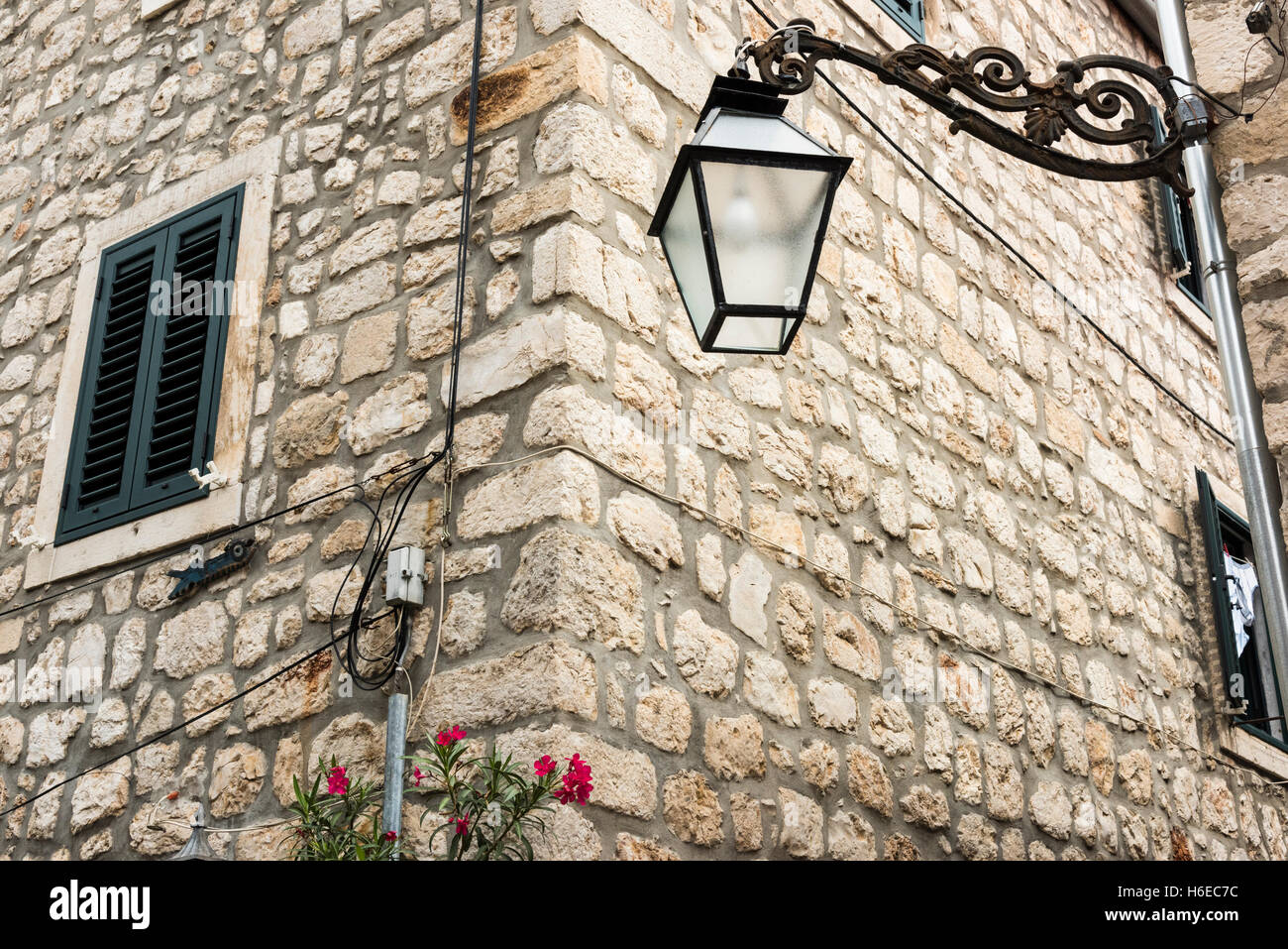 A wrought Iron street lamp on an old stone building at Ston Croatia - Stock Image