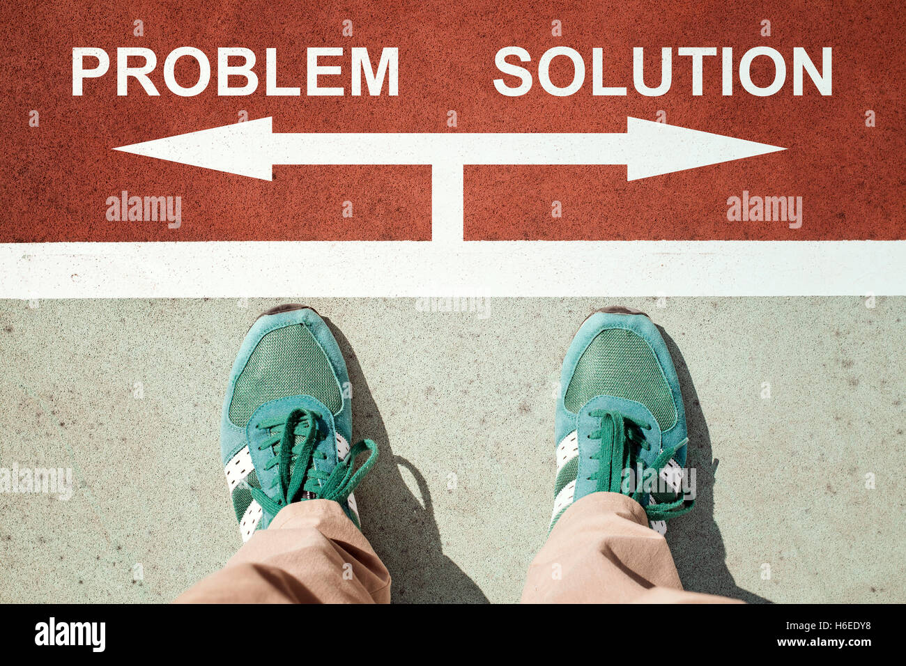 Problem or solution concept with legs from above standing on signs - Stock Image