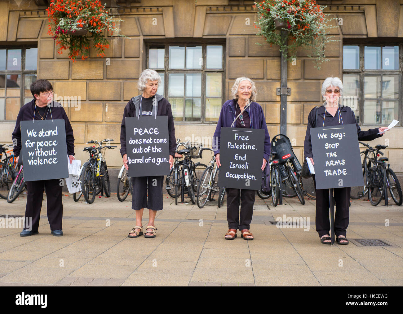 four older ladies making a peace protest in Cambridge Market square  'we stand for peace without violence' - Stock Image