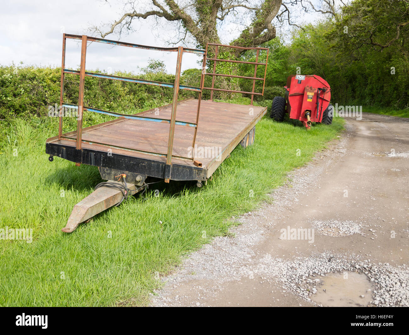 trailer and muck spreader at side of country lane - Stock Image