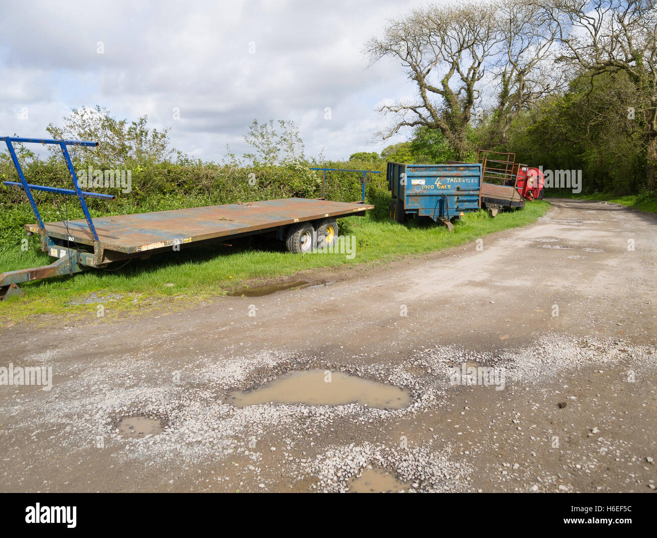 trailers and muck spreader at side of country lane - Stock Image
