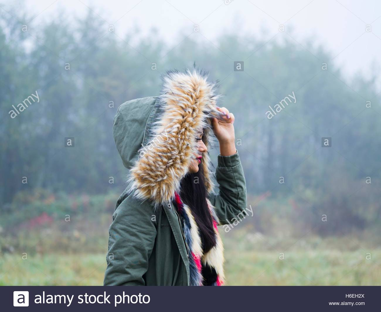 Under hood cold weather walking walk girl outdoors foggy day side view forest in nature hoodie single Stock Photo