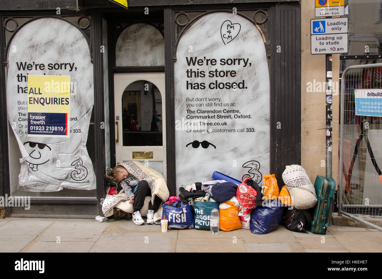 Young homeless woman sleeping outside a closed shop in Cornmarket street, Oxford city center - Stock Image