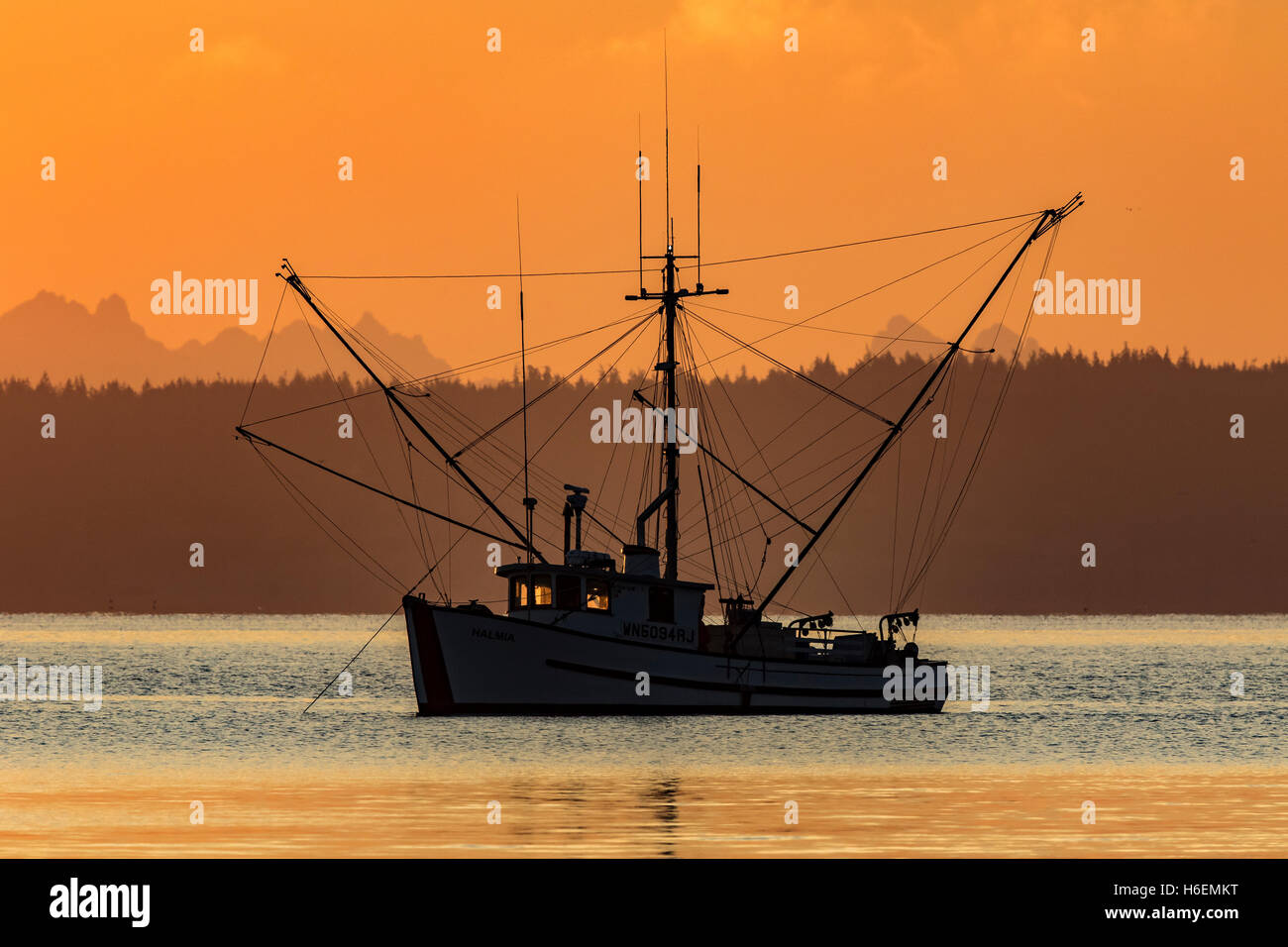 Fishing boat troller at anchor during sunrise in Port Townsend, Puget Sound. Salmon fishing boat. - Stock Image