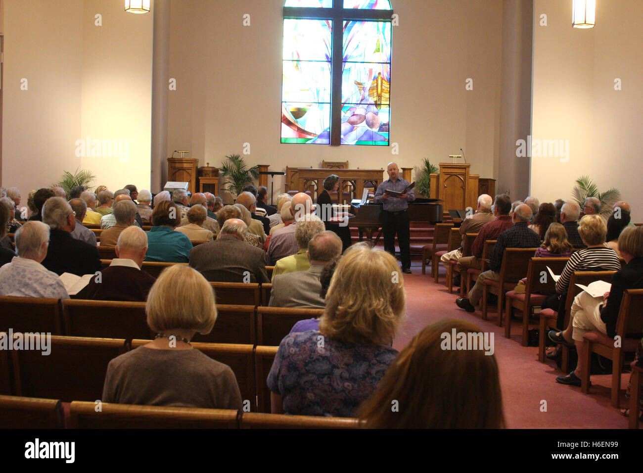 Singer and piano player having a public performance in church - Stock Image