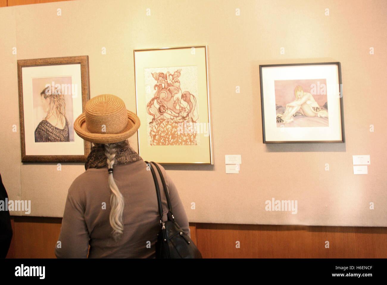 People looking at art display in gallery - Stock Image