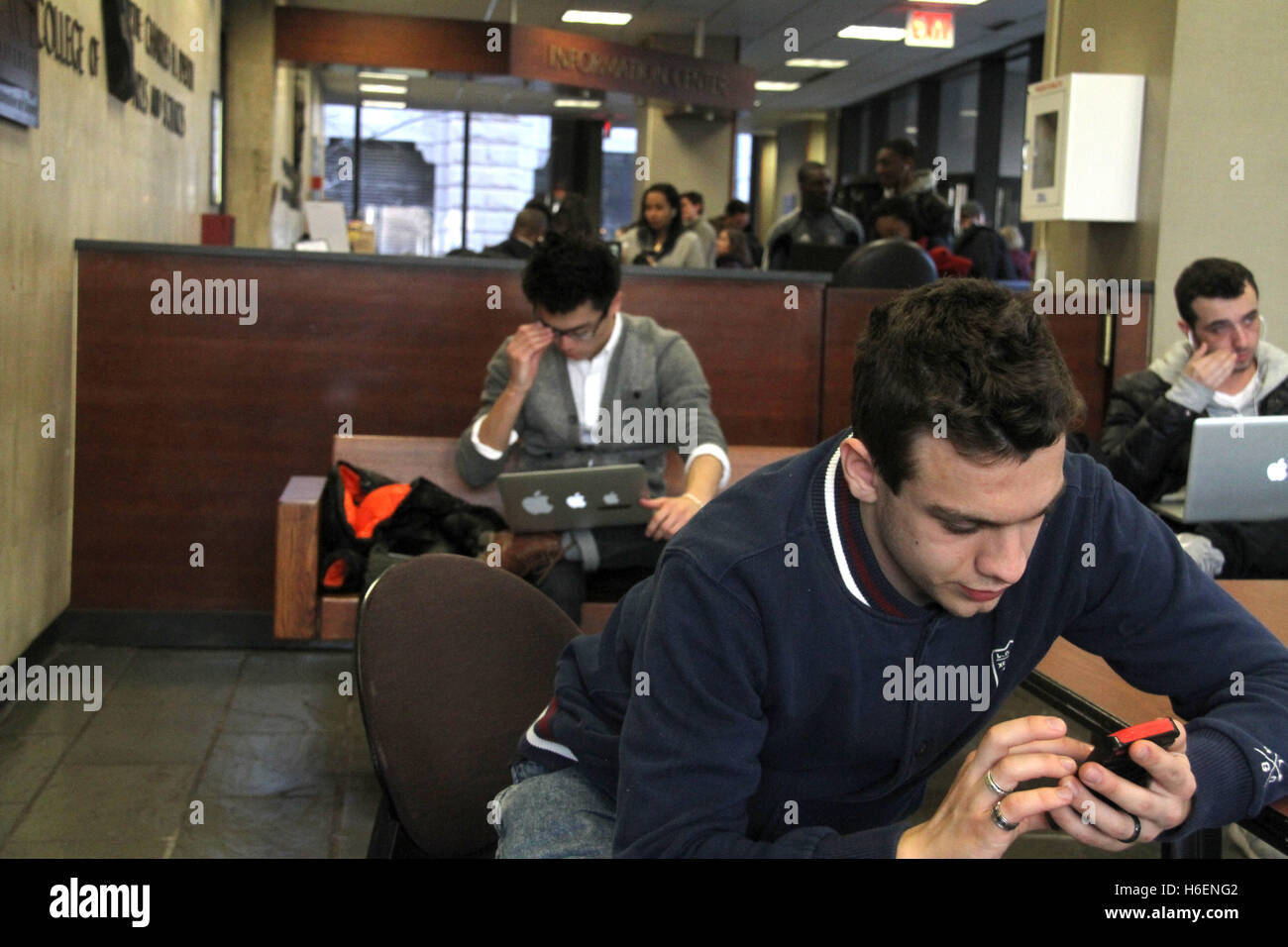 Young people on digital gadgets inside restaurant - Stock Image