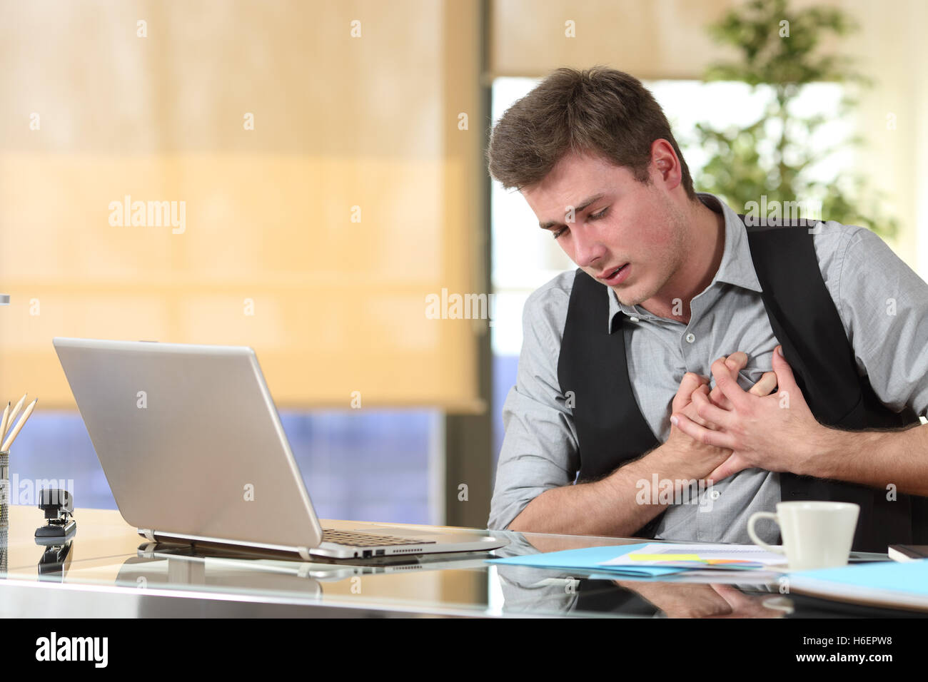 Businessman suffering a heart attack with his hands grabbing the chest sitting in a desktop at office - Stock Image