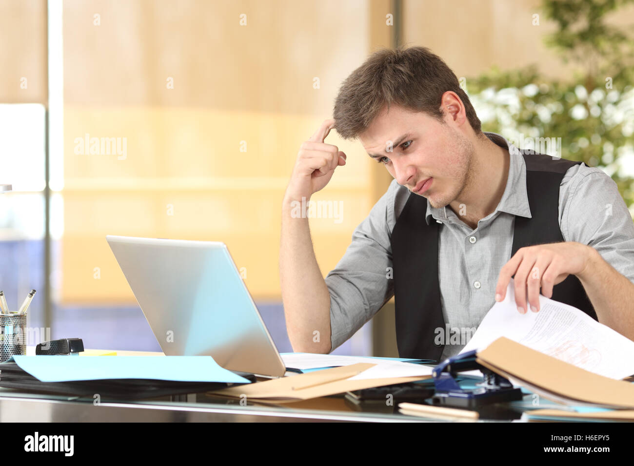 Incompetent businessman thinking how to do his job online with messy desk at office - Stock Image