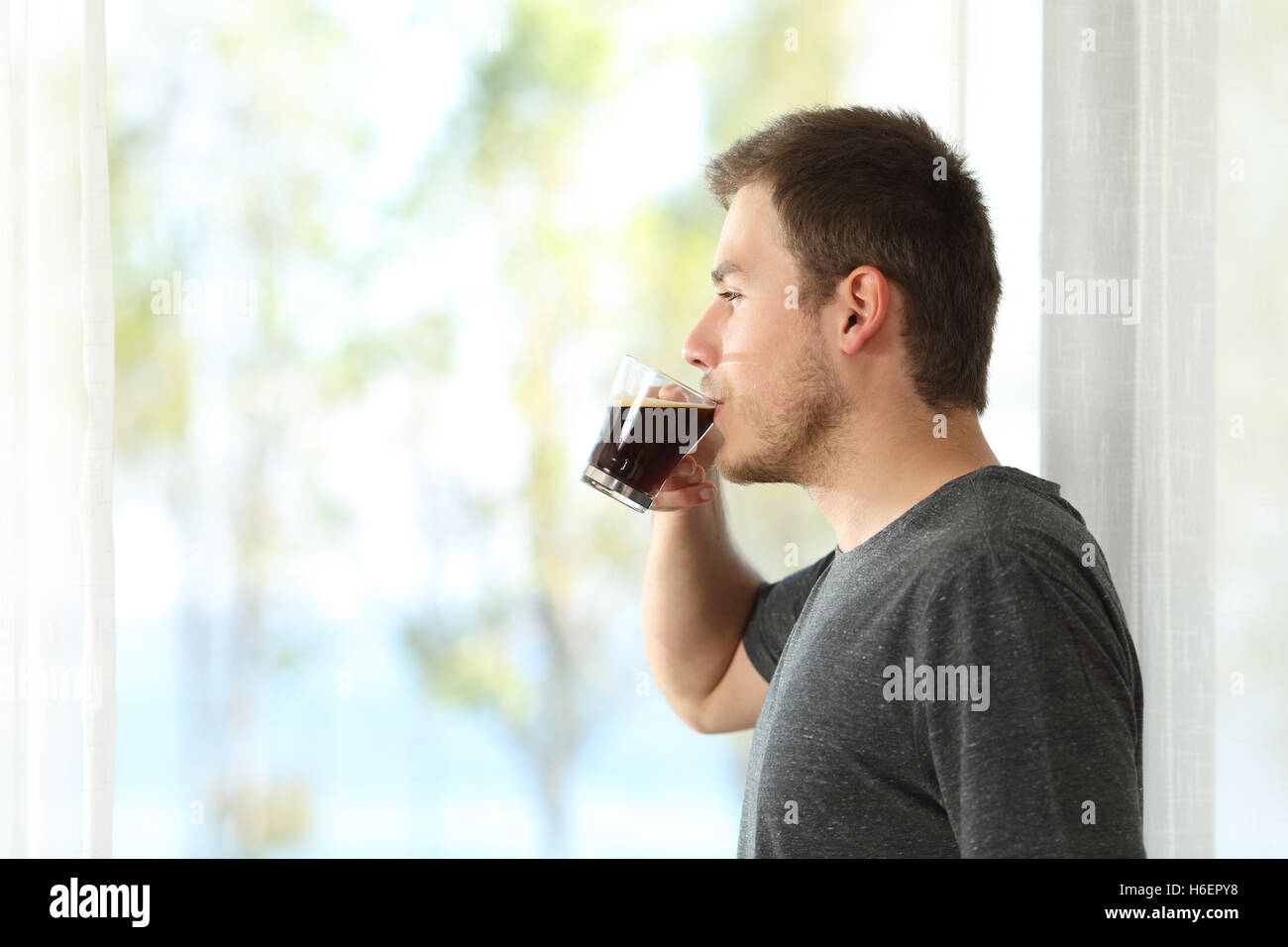 Side view of a man drinking coffee looking through the window of home or hotel - Stock Image