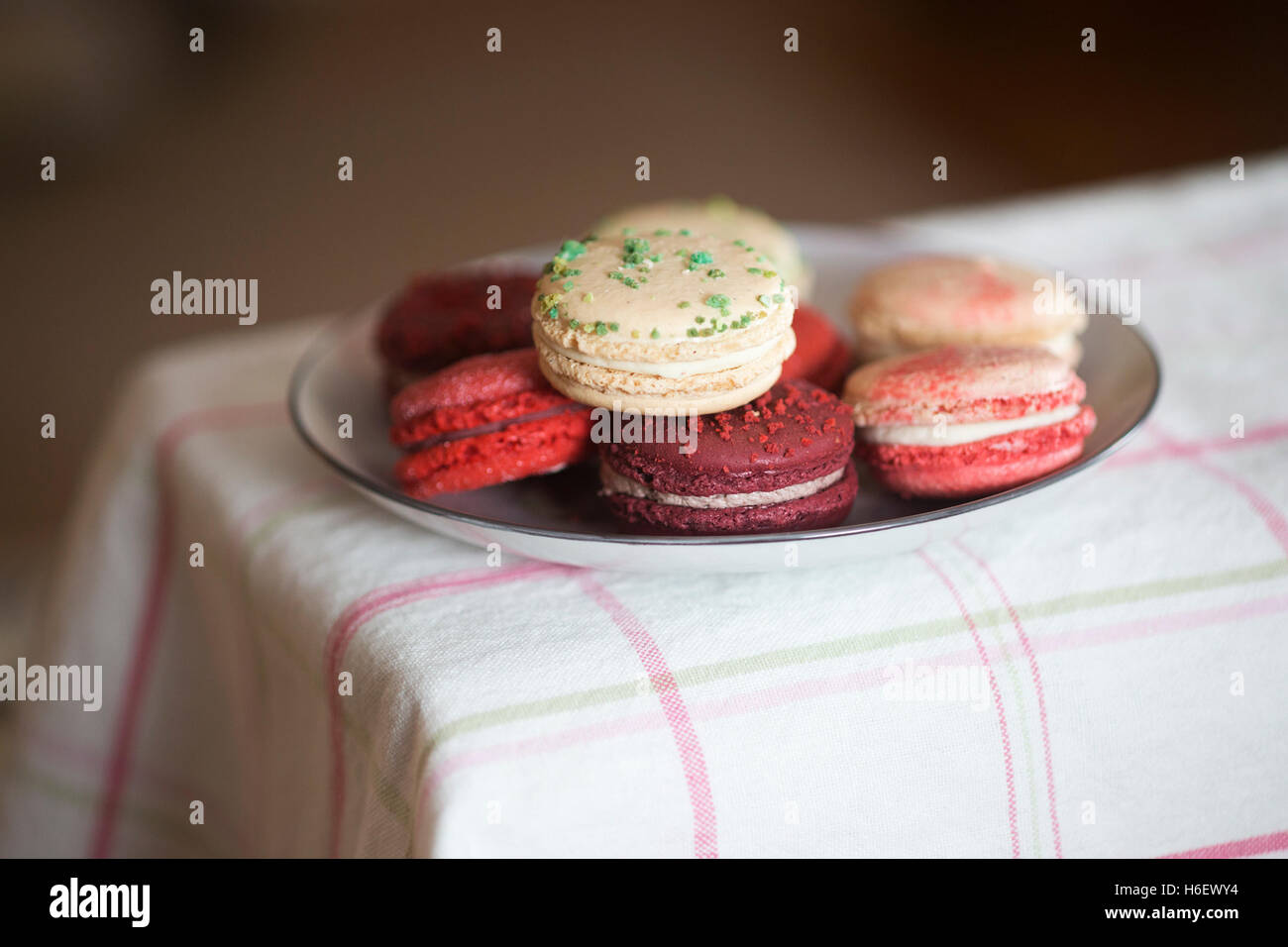 Christmas macarons - vanilla basil, frosted cranberry, mulled wine and candycane flavours on checked tablecloth - Stock Image