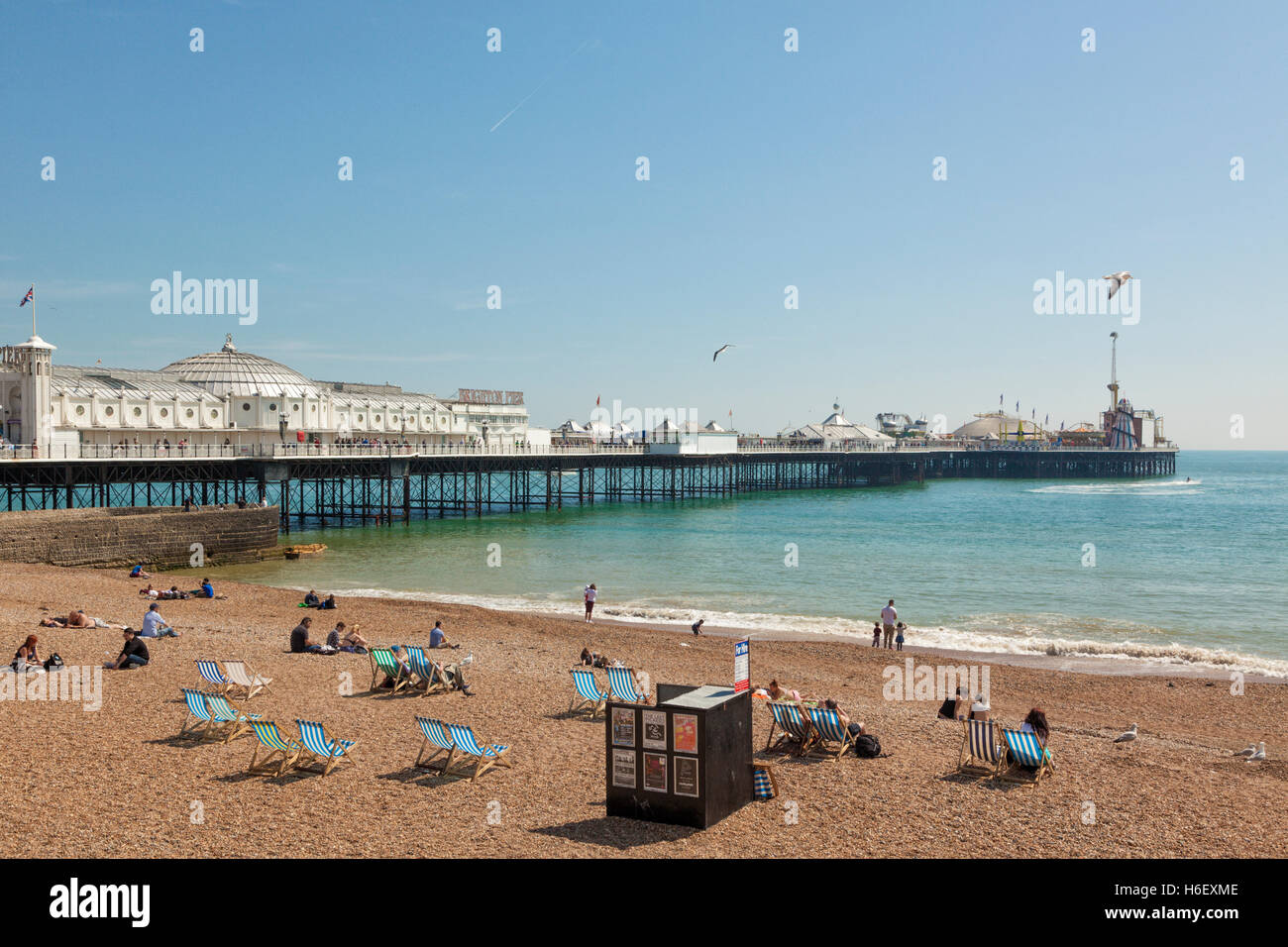 Pier of Brighton, people on the beach in front - Stock Image