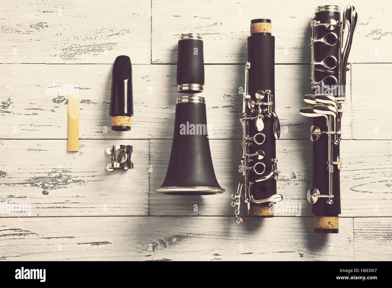 overhead of a disassembled clarinet on wood top - Stock Image