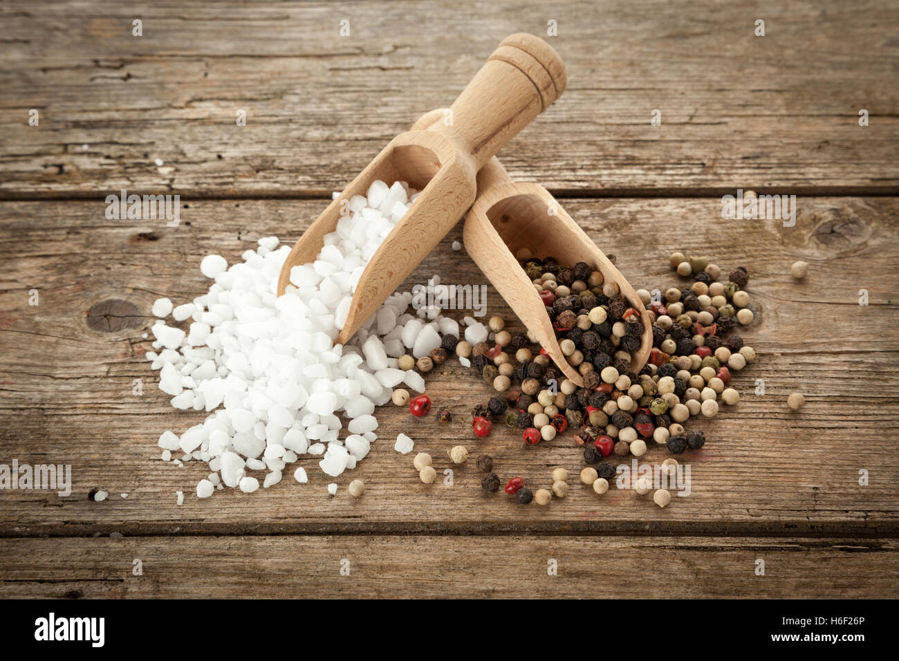 Large-grained salt and mixed peppercorns on wooden shovels, on rustic table, high angle view - Stock Image
