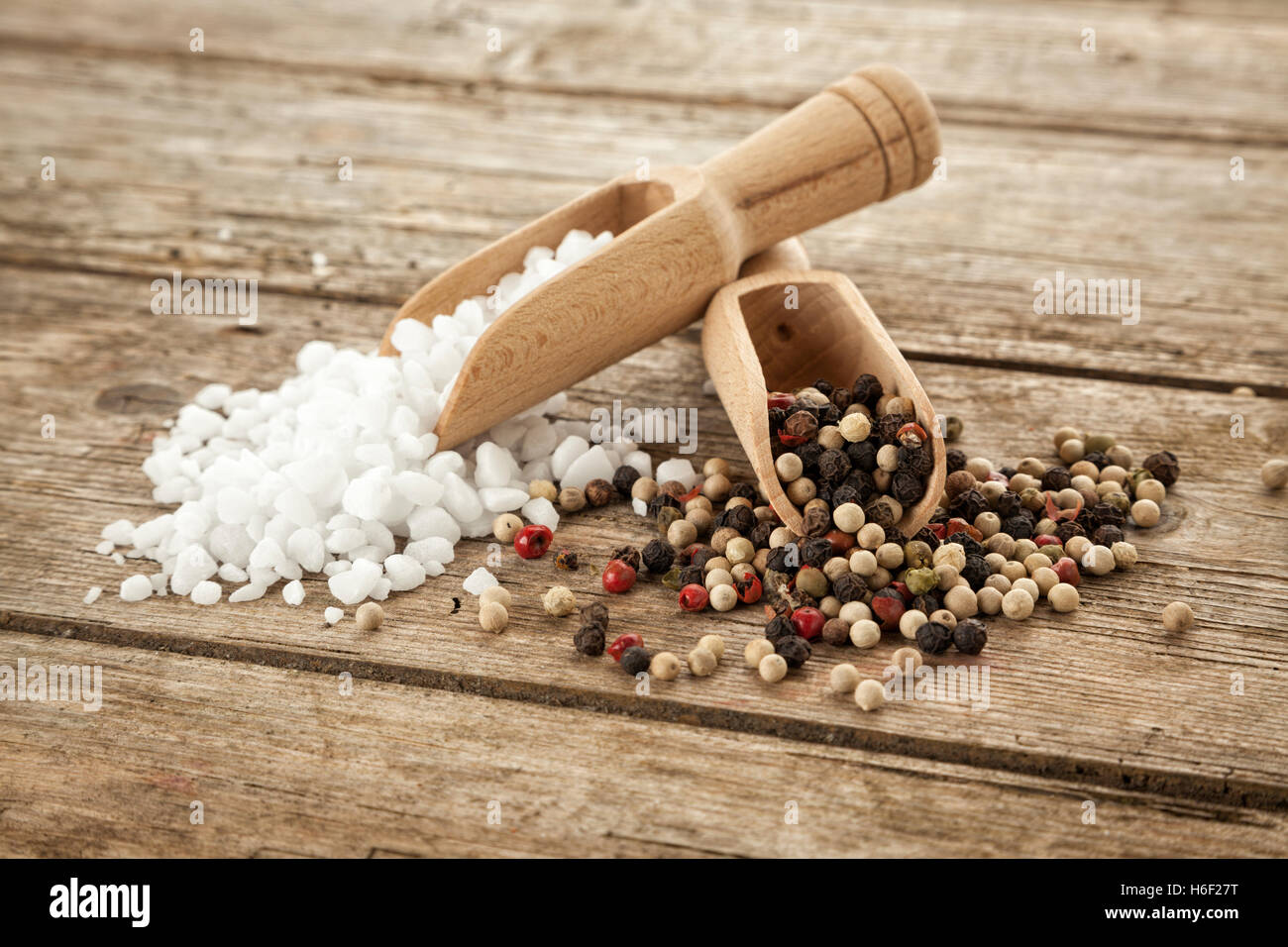 Large-grained salt and mixed peppercorns on wooden shovels, on rustic table - Stock Image